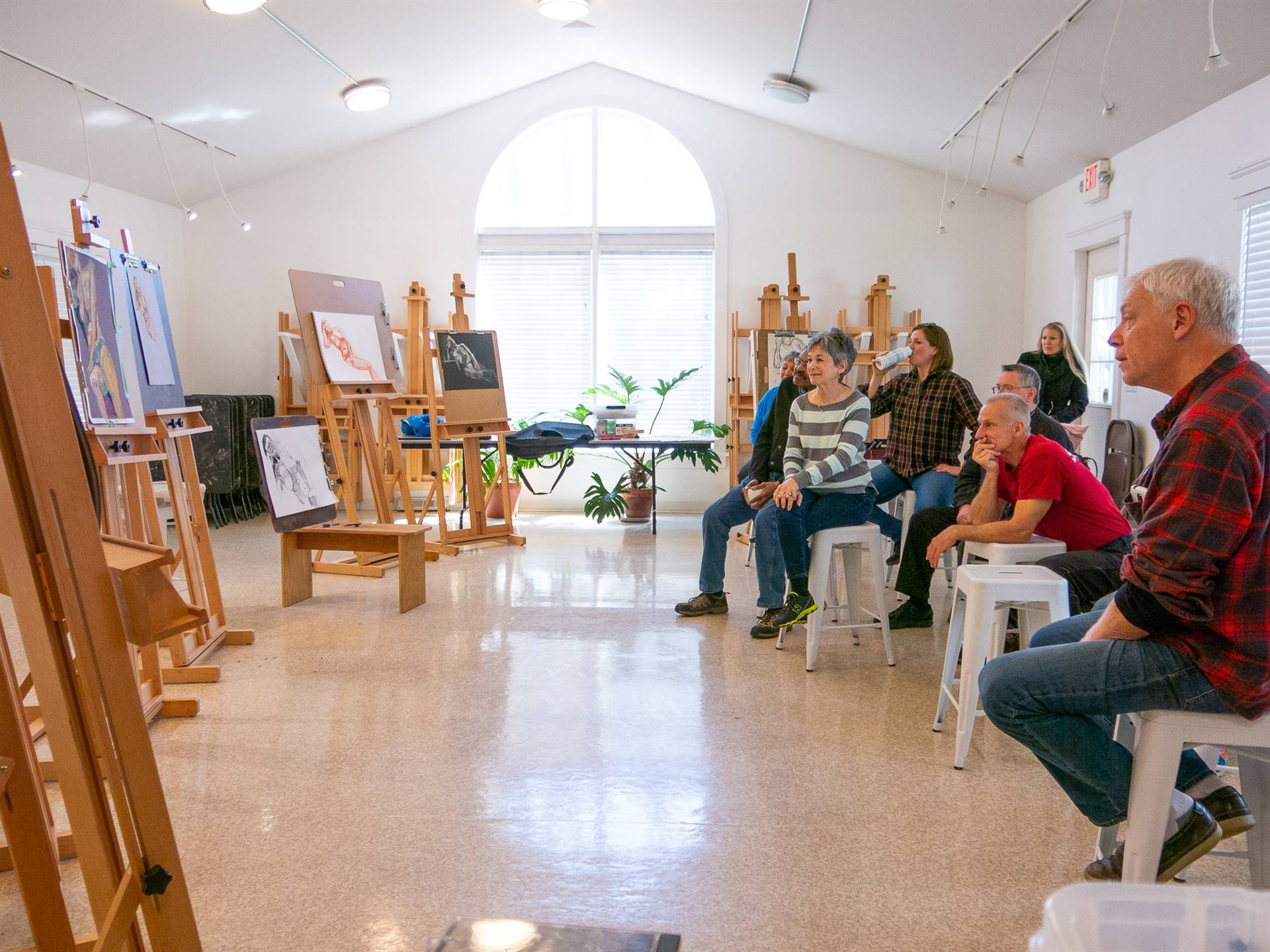 Art participants studying paintings on easels
