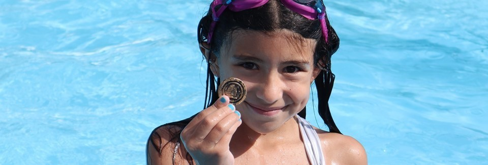 Girl holding treasure hunt coin found in the pool during special event