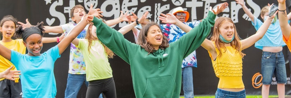 Teenage children with their hands in the air singing outdoors against a black backdrop